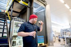 Med skjegg og lue på: Mike Murphy kvalitetssikrer et av produktene til Lervig. (Foto: Skjalg Ekeland/ Den norske ølrevolusjonen)